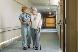 Nurse helping elderly woman walk down hallway